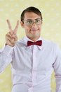 Geek gesturing peace sign portrait of male over yellow textured background Stock Photography