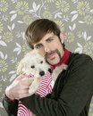 Geek retro man holding dog silly on wallpaper Stock Image