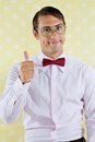 Geek wishing luck portrait of young male gesturing thumbs up over yellow textured background Royalty Free Stock Image