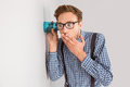 Geeky businessman eavesdropping with cup Royalty Free Stock Photo