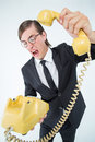 Geeky businessman shouting and hanging up the telephone on white background Stock Images