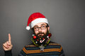Geeky young man in santa claus hat pointing up Royalty Free Stock Photo