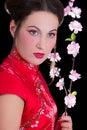 Geisha hermoso joven con las flores de sakura aisladas en negro Imagenes de archivo