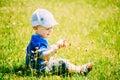 Gelukkig little boy kind sit in summer green grass Stock Foto's