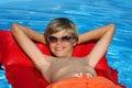 Gelukkige jongen die met zonglazen op luchtbed ontspant Stock Afbeelding