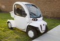 Gem e electric car white used as an alternative to golf carts great for neighborhood transportation stands for global Royalty Free Stock Photo
