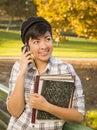 Gemengde ras vrouwelijke student holding books en het spreken op telefoon Royalty-vrije Stock Afbeeldingen