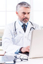 General practitioner mature grey hair doctor working on laptop while sitting at his working place Royalty Free Stock Photos