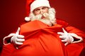 Generosity portrait of santa claus embracing huge red sack with gifts Stock Images