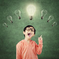 Genius child pointing at bright light bulb Royalty Free Stock Photo