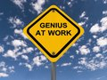 Genius at work sign a typical yellow road with black upper case text saying set against a blue cloudy sky Royalty Free Stock Photography