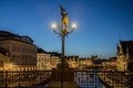 Gent night belgium a statue on a lamp on a bridge over one of the canals and the historical buildings lit at Royalty Free Stock Photos