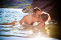 Gentle kiss in water at sunset with wet dress Stock Photos