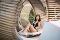 Gentle lady sitting in black bikini on original wooden lounger with white mattress among other similar sunbeds Royalty Free Stock Photo