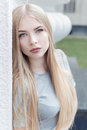 Gentle portrait of a beautiful cute girl with long blond hair with full lips and blue eyes in a gray suit, look at the camera Royalty Free Stock Photo