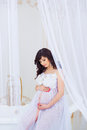 Gentle pregnancy. Beautiful pregnant in light white dress with orchids