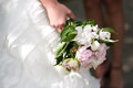 Gentle wedding bouquet with peonies in hands of the bride Royalty Free Stock Photo