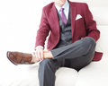 Gentleman burgundy blazer double monk shoes young male model on a white sofa wearing a and brown leather Royalty Free Stock Photo