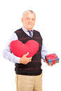 Gentleman holding a heart shaped object and gift Royalty Free Stock Photo