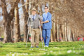 Gentleman and a male nurse walking in park on sunny day Royalty Free Stock Image