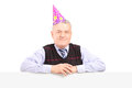 Gentleman wearing party hat and posing behind a panel Stock Image