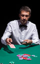 Gentleman in white shirt playing cards on black background Stock Photo