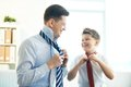 Gentlemen photo of happy boy and his father tying neckties Royalty Free Stock Photography