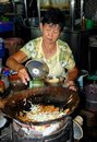 Georgetown, Malaysia: Woman Cooking with Wok Stock Photo