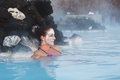 Geothermal spa woman relaxing in in hot spring pool in iceland girl enjoying bathing in a blue water lagoon with famous healing Stock Images