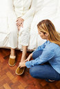 Geriatric caregiver helping senior woman women putting on slippers Stock Photography