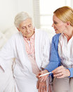 Geriatric nurse with fever Royalty Free Stock Photography