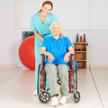 Geriatric nurse with old woman in wheelchair women at physiotherapy Stock Photography