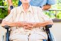 Geriatric nurse pushing senior lady in wheel chair thru home Stock Photo