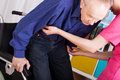 Geriatric patient sitting on wheelchair with help of nurse Royalty Free Stock Photos