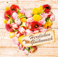 German birthday wishes on a colourful floral heart formed of fresh spring tulips in vibrant colours arranged rustic wooden Stock Photography