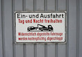 German no parking sign warning on garage door written in language with silhouette of vehicle being towed away Royalty Free Stock Photos