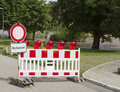 German sign warning of a flooded area somewhat worn down road block ahead partly park in the background Royalty Free Stock Photography