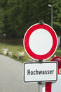 German sign warning of a flooded area somewhat worn down road block ahead very shallow depth field for generic usability Royalty Free Stock Photo