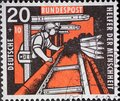 GERMANY - CIRCA 1957: This charity postage stamp shows a miner coal mining on the conveyor belt. The background color is red Royalty Free Stock Photo