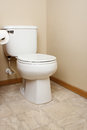 Gerneric white toilet in bathroom tan walled Stock Photography