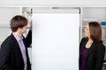 Geschäftsfrau with coworker looking bei flip chart Lizenzfreies Stockbild