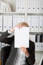 Geschäftsfrau holding blank paper in front of face Lizenzfreies Stockbild