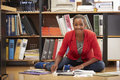 Geschäftsfrau sitting on office boden lesedokumente Stockfotografie