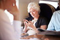 Geschäftsfrau using mobile phone auf beschäftigtem nahverkehrszug Stockbild