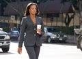 Geschäftsfrau walking along street das mitnehmerkaffee hält Stockfotografie