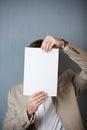 Geschäftsmann holding blank paper in front of face Stockbild