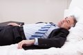 Geschäftsmann relaxing on bed Lizenzfreies Stockfoto