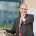 Geschäftsmann showing thumbs up zeichen am podium Lizenzfreies Stockfoto