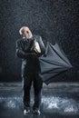 Geschäftsmann struggling to open regenschirm im regen Stockfotos