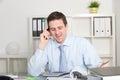Geschäftsmann talking through phone in seinem büro Stockbilder